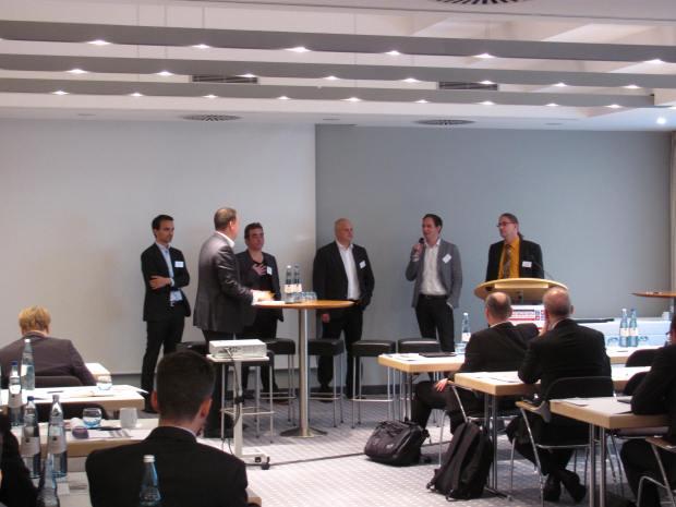 Die fünf Teilnehmer der Podiumsdiskussion, zum Publikum gewendet. Von links nach rechts: Adrian Hotz, Jörg Platzer, Holger Klemusch, Florian Moser und Jens Münzer.